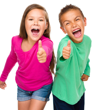 cool kids: Little boy and girl are showing thumb up sign, isolated over white Stock Photo