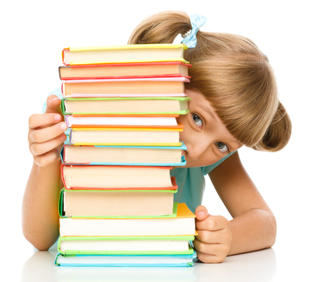 kids reading: Cute little girl plays with pile of books while sitting at table, isolated over white Stock Photo