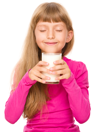 one eye closed: Happy little girl with a glass of milk, isolated over white Stock Photo