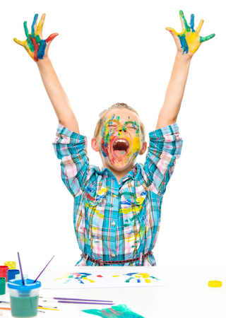 Little girl is rising her hands up in joy while playing with paints, isolated over white photo