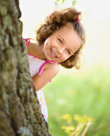 hide and seek: Cute little girl is playing hide and seek, outdoor shoot