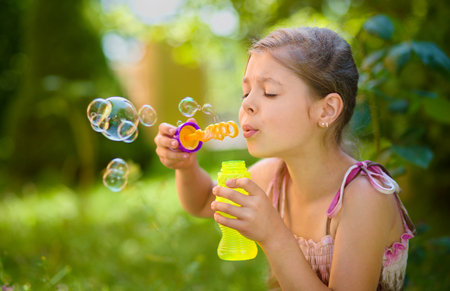 blowing bubbles: Cute little girl is blowing a soap bubbles, outdoor shoot Stock Photo