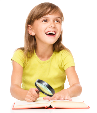 erudition: Little girl is reading book using magnifier while sitting at table, isolated over white Stock Photo
