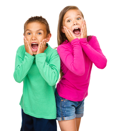 astonishment: Portrait of cute girl and boy holding their faces in astonishment, isolated over white Stock Photo