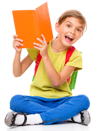 Portrait of a cute little schoolgirl with backpack hiding behind book, isolated over white