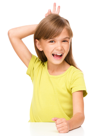 exhilarated: Portrait of a happy little girl laughing and making horns or bunny ears, isolated over white