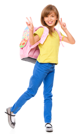 Little schoolgirl with a backpack showing victory sign, isolated over white photo