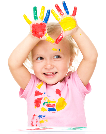 playschool: Portrait of a cute little girl showing her hands painted in bright colors, isolated over white