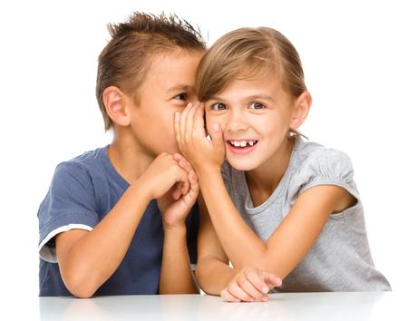 niños platicando: Niña y niño están susurrando en el oído, aislado más de blanco Foto de archivo