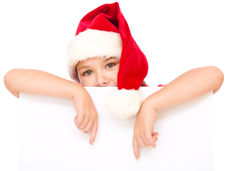 Little girl in santa hat is holding blank board and pointing to it using index finger, isolated over white photo
