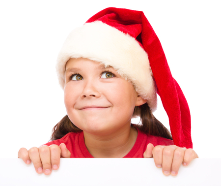 blank banner: Little girl in santa hat is holding blank board and smiling, isolated over white