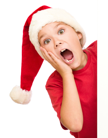 santa girl: Little girl is holding her face in astonishment standing near blank board, isolated over white Stock Photo