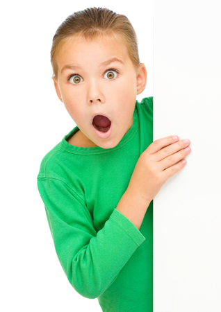 girl open mouth: Little girl is looking out from the blank banner, opening her mouth in astonishment, isolated over white