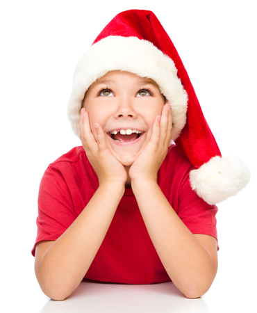 and guessing: Little girl in santa hat is daydreaming supporting her head with hands, isolated over white Stock Photo