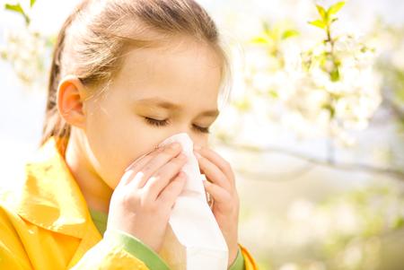 tosiendo: Niña sopla su nariz cerca del árbol de la primavera en flor