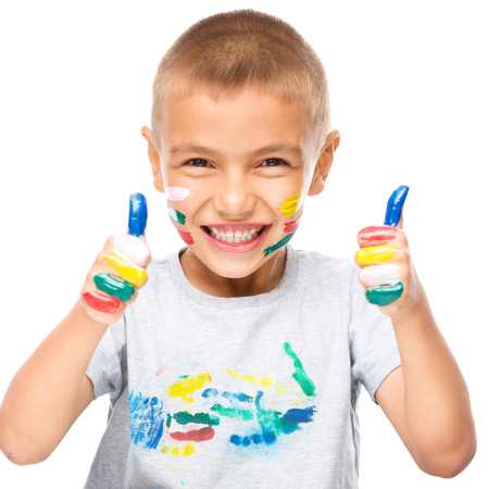 playschool: Portrait of a cute boy playing with paints and showing thumb up sign using both hands, isolated over white