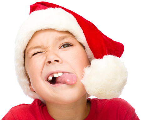 sticking: Little girl in santa hat is trying to touch the pompon with her tongue, isolated over white