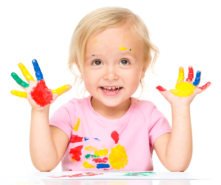 fingerpaint: Portrait of a cute little girl showing her hands painted in bright colors, isolated over white