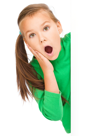girl open mouth: Little girl is looking out from the blank banner, holding her face in astonishment, isolated over white