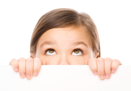 interested: Little girl is looking from out blank board, isolated over white Stock Photo