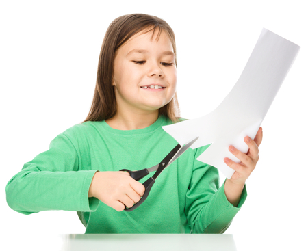 scissors cutting paper: Little girl is cutting paper using scissors while sitting at table, isolated over white