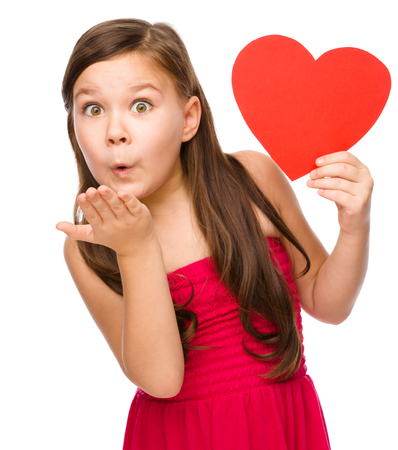 Little girl is holding red heart and blowing a kiss, isolated over white Banque d'images