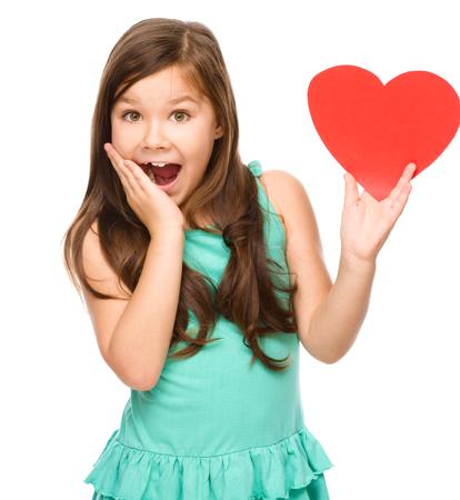 astonishment: Ni�a con el coraz�n rojo, sosteniendo su cara de asombro, el concepto de Valentine, aislado m�s de blanco Foto de archivo