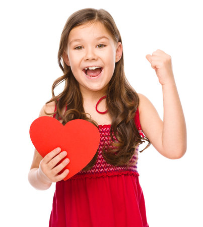 young girl smiling: Little girl with red heart, holding her face in astonishment, Valentine concept, isolated over white