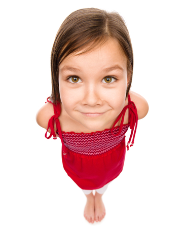angle views: Happy little girl in red dress, fisheye portrait, isolated over white