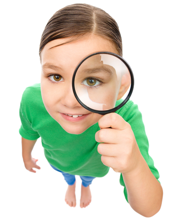 top angle view: Funny little girl is looking through magnifier, fisheye portrait, isolated over white