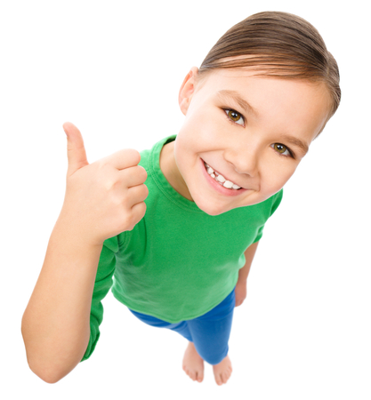 top angle: Little girl is showing thumb up gesture, fisheye portrait, isolated over white