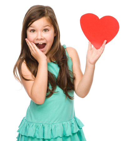 euphoric: Little girl with red heart, holding her face in astonishment, Valentine concept, isolated over white