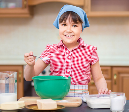 adding sugar: Girl is cooking, adding a spoon of sugar to bowl, indoor shoot