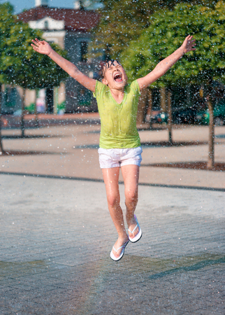 water splashing: Hot summer in the city - girl is running through fountains