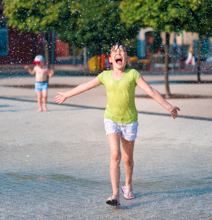 fountain: Hot summer in the city - girl is running through fountains