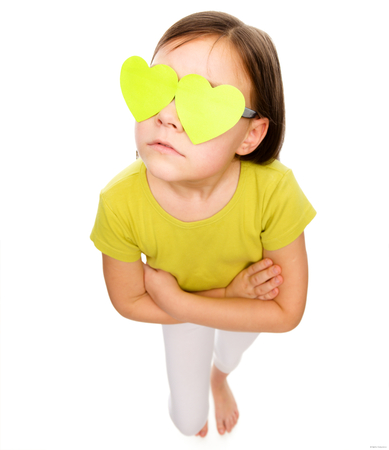 Little girl is holding hearts over her eyes, fisheye portrait, valentine concept, isolated on white Stock Photo