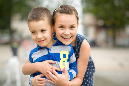 kids hugging: Children are playing in summer city, outdoor shoot