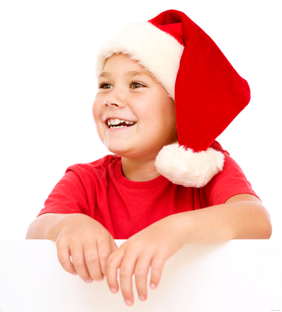 wishful: Little girl in santa hat is holding blank board and smiling, isolated over white