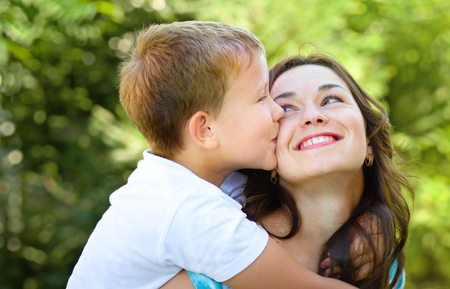 Son is kissing his happy mother, outdoor shoot Imagens
