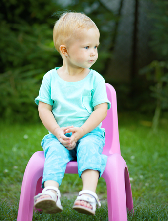 Portrait of a child sitting on plastic chair, outdoor shoot Imagens