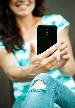 Cheerful woman is using her smartphone Imagens