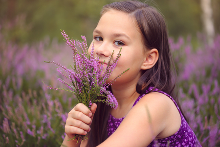 brunette girl: Girl is holding bunch of heather flowers, outdoor shoot Stock Photo