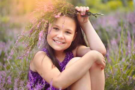 Girl is holding bunch of heather flowers, outdoor shoot Imagens