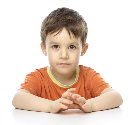 Portrait of a cute little boy sitting at table and fixing his eyes on you, isolated over white photo