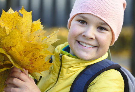 Cute little girl in autumn park holding bunch of yellow leaves photo