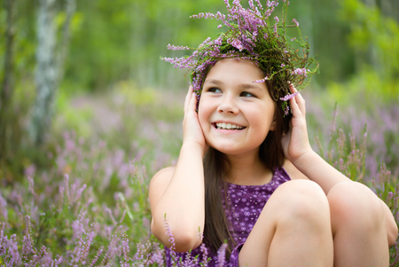 Girl is holding wreath of heather flowers, outdoor shoot photo