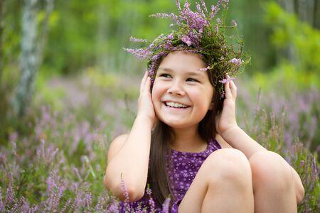 Happy girl is wearing heather wreath, outdoor shoot