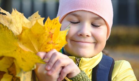 Cute little girl closed her eyes in happiness in autumn park holding bunch of yellow leaves, outdoor shoot