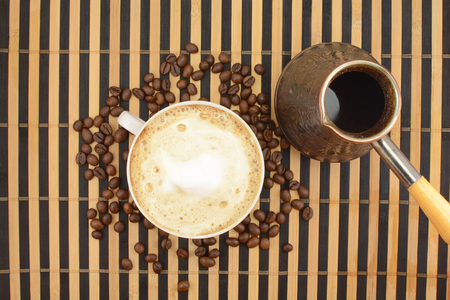 coffee pot: coffee on the background of coffee beans with foam, coffee pot on a striped background, Coffee Pot Stock Photo