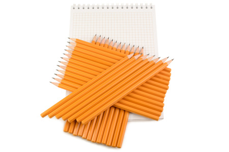 supplies: several stacked pencil lie on a notebook on a white background Stock Photo